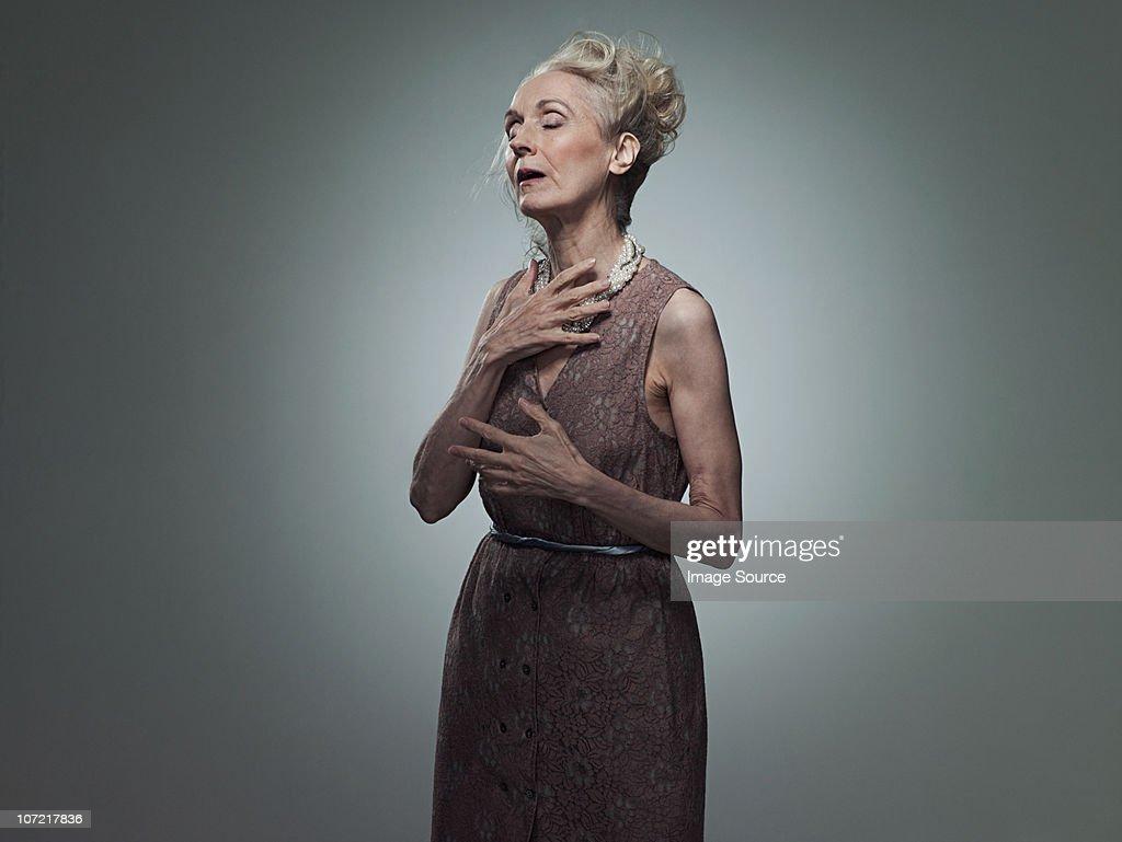 Senior woman touching chest, portrait : Stock Photo