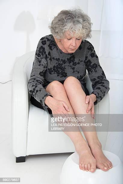 Senior woman touching her legs