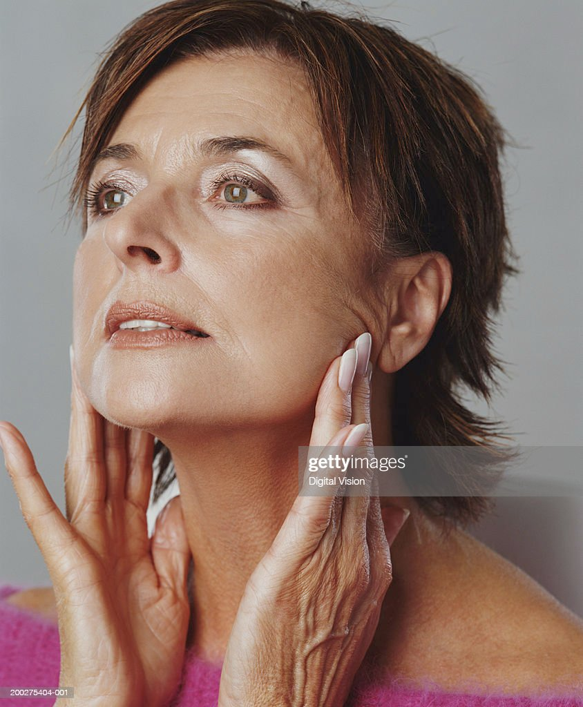 Senior woman touching jaw line with fingers, close-up : Stock Photo