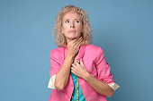 senior caucasian blonde woman touching painful