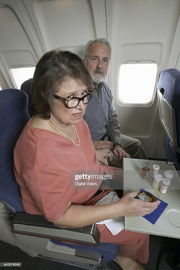 Senior Woman Travel Sick During a Flight on a Commercial Aeroplane : Stock Photo