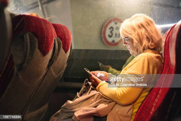 Senior woman traveling by bus while texting with her mobile phone