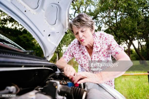 Senior vrouw tevergeefs trying voor positiebepaling achtergebleven auto