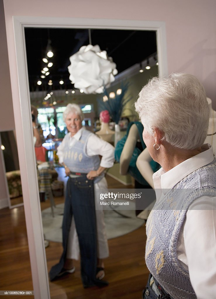 Senior woman trying on clothing in store : Foto stock