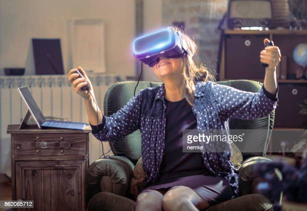 senior woman trying virtual reality headset - futurism stock photos and pictures