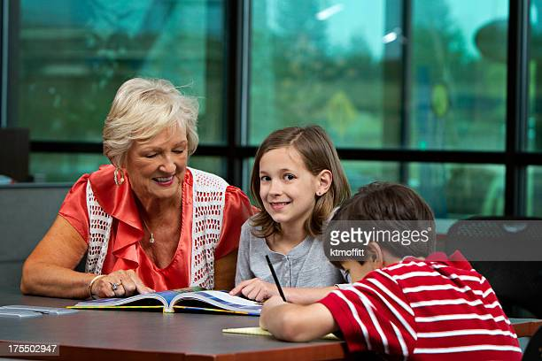 Senior Frau Tutoring Kinder In Bibliothek