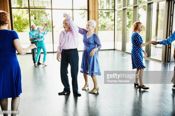 Senior woman twirling partner while dancing in community center