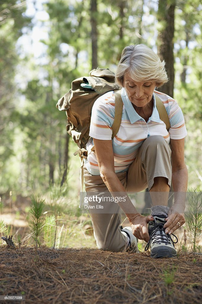 Senior Woman Tying the Laces of Her Walking Boots in Woodland During a Hike : Stock Photo