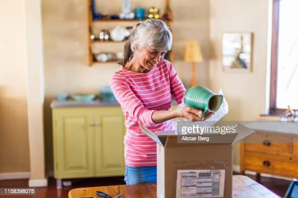 senior woman unpacking a package from an online purchase - receiving stock pictures, royalty-free photos & images