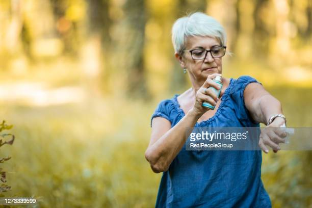 senior woman  use of insect repellent in the woods - insect bites images stock pictures, royalty-free photos & images