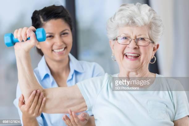 Senior woman uses barbell to regain shoulder strength
