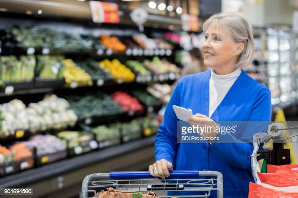 Senior woman uses shopping list to selective produce at grocery store