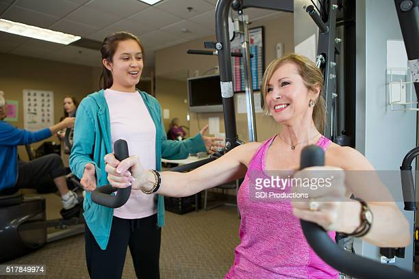 Senior woman uses weight machine in gym