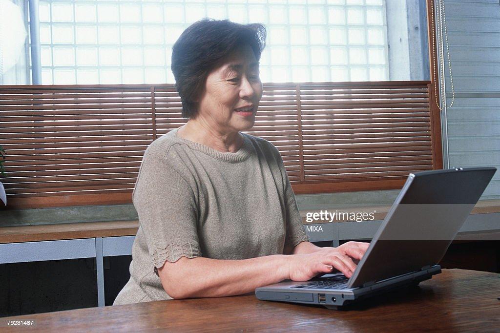 A senior woman using a computer : Stock Photo