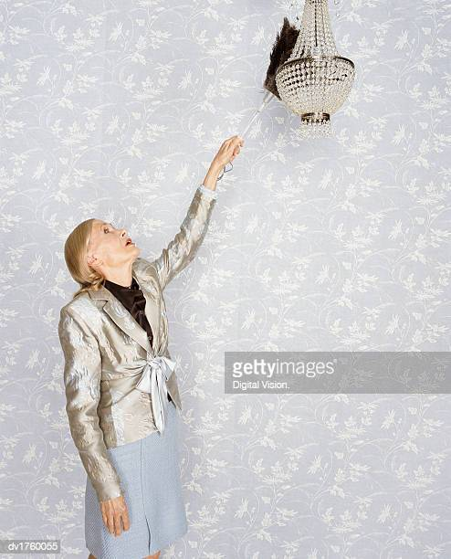 Senior Woman Using a Feather Duster to Clean a Chandelier