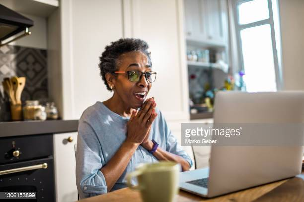 senior woman using a laptop - using laptop stock pictures, royalty-free photos & images
