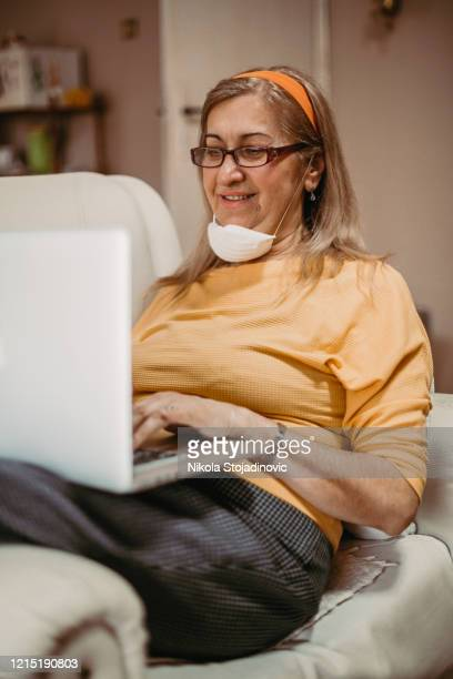 senior woman using a laptop to connect with her friends and family during quarantine - video still stock pictures, royalty-free photos & images