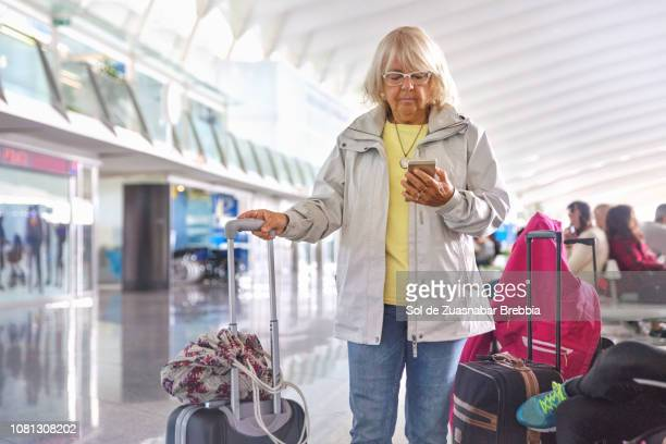 Senior woman using a mobile device at the airport