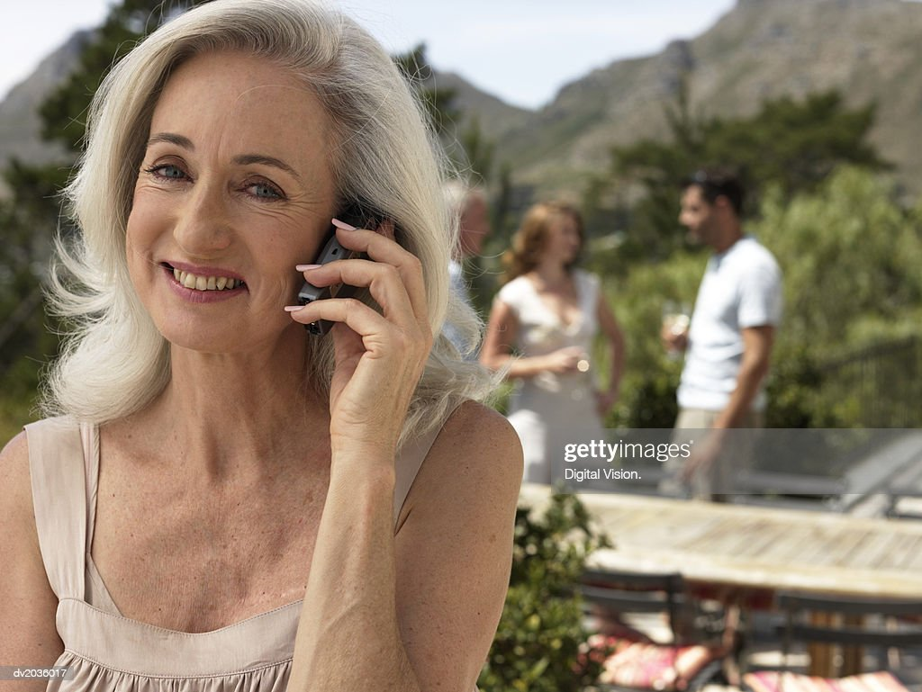 Senior Woman Using a Mobile Phone With a Group of People Drinking Wine Outdoors in the Background : Stock Photo