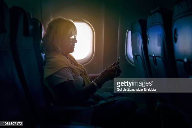 Senior woman using a smartphone on a plane
