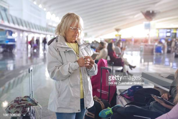 Senior woman using a smartphone while waiting in a bright airport