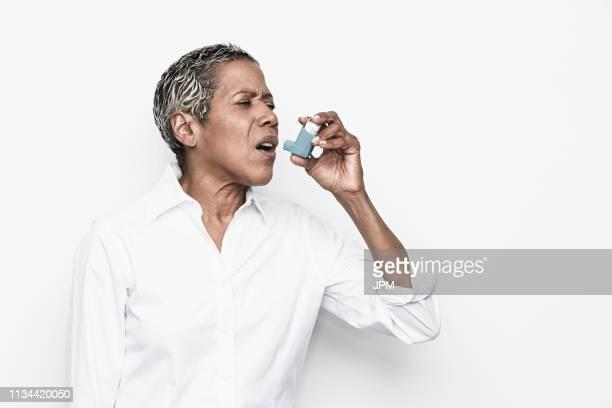 senior woman using asthma inhaler - bomba para asma imagens e fotografias de stock