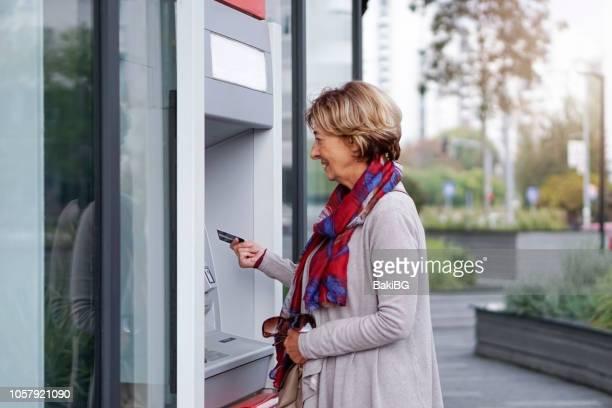 ältere frau mit atm in der stadt - geldautomat stock-fotos und bilder