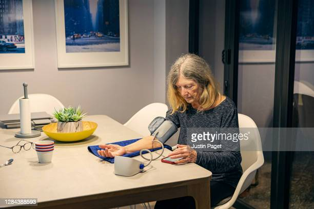 senior woman using blood pressure monitor - medicine stock pictures, royalty-free photos & images