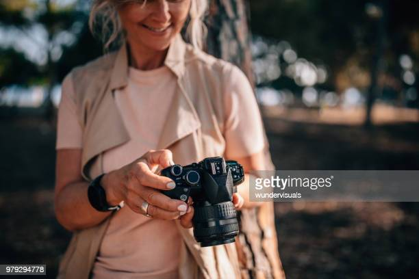 senior woman using camera and looking at photos in nature - photographer stock photos and pictures