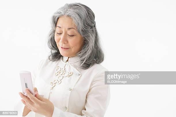 Senior woman using cellular phone, studio shot