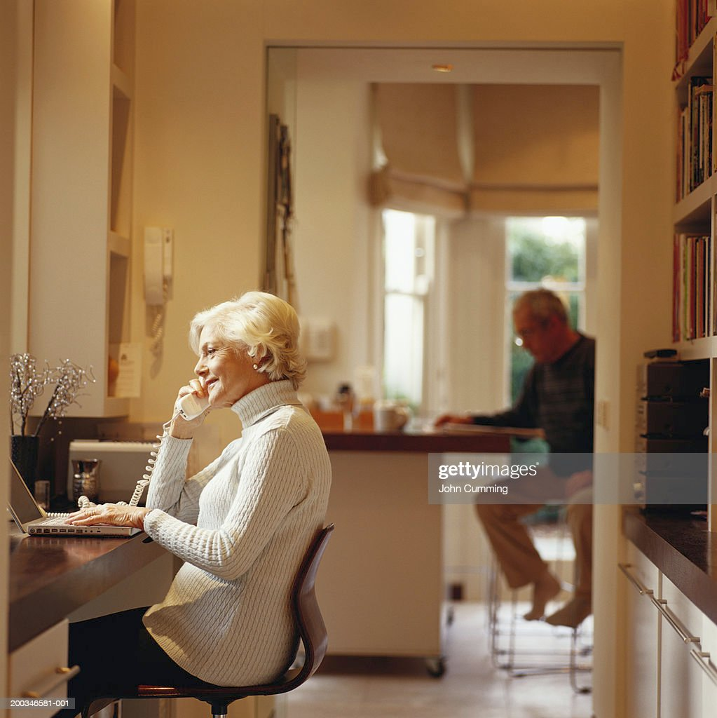 Senior woman using computer and telephone, senior man in background : Stock-Foto