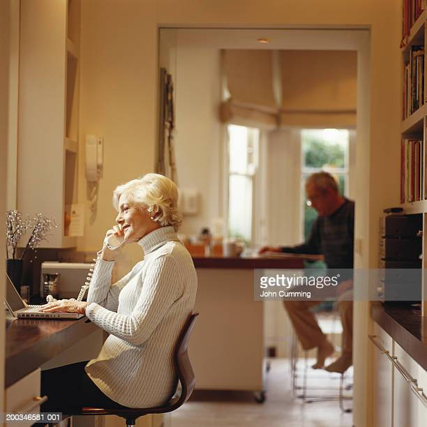 Senior woman using computer and telephone, senior man in background