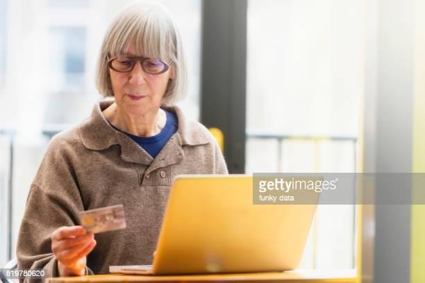 Senior vrouw met behulp van creditcard op internet