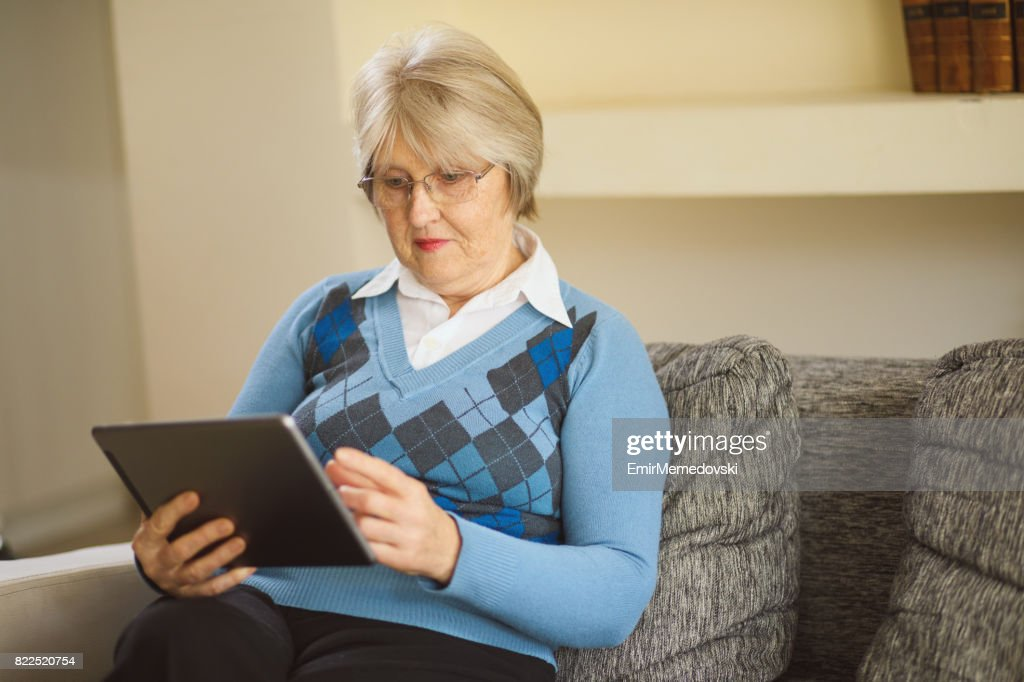Senior woman using digital tablet at home : Stock Photo