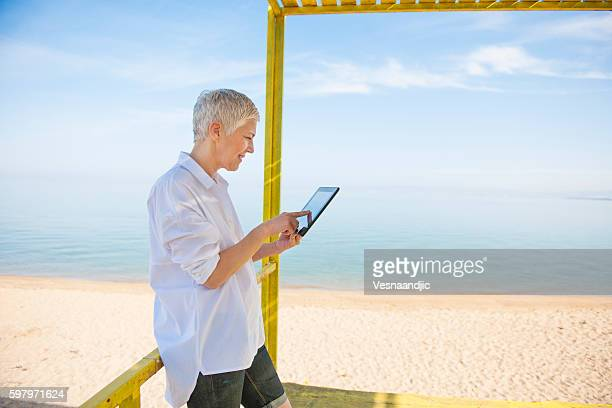 Senior woman using digital tablet at the beach