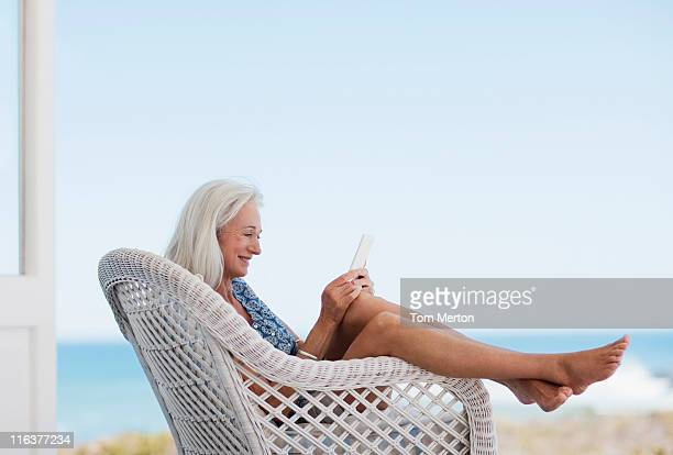 senior woman using digital tablet in chair - feet up stock pictures, royalty-free photos & images
