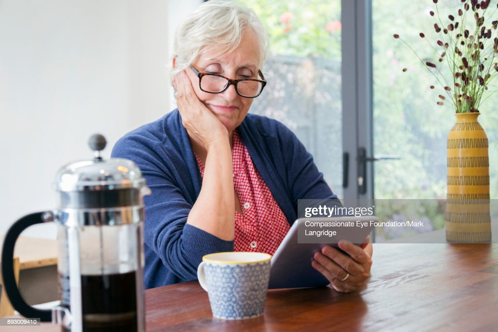 Senior woman using digital tablet in kitchen : Stock Photo