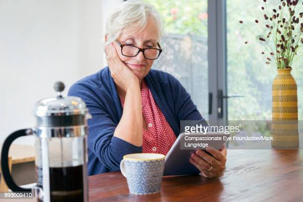 senior woman using digital tablet in kitchen - reading glasses stock pictures, royalty-free photos & images