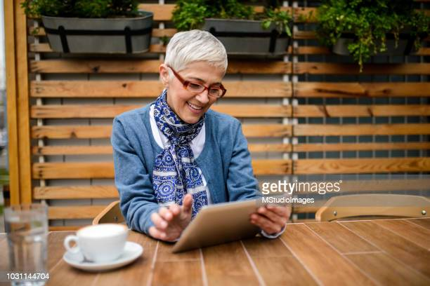 senior woman using digital tablet. - white hair stock pictures, royalty-free photos & images