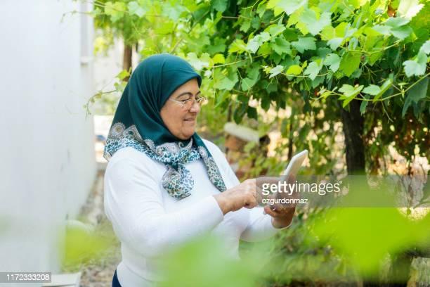 femme aîné utilisant la tablette numérique - chubby arab photos et images de collection