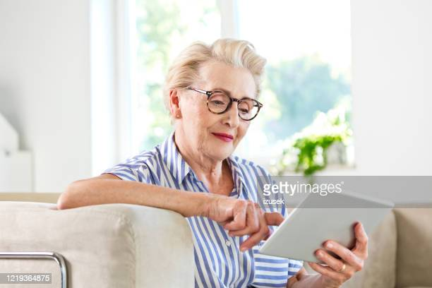 senior woman using digital tablet together at home - izusek stock pictures, royalty-free photos & images