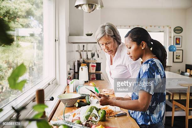 Senior woman using digital tablet with daughter-in-law while cooking food in kitchen