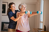 old woman training with physiotherapist using
