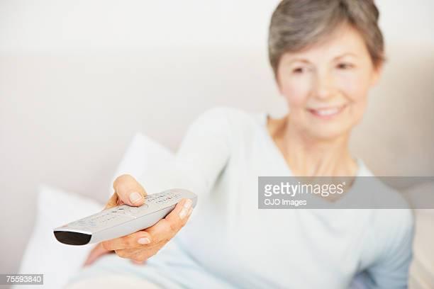 シニア女性彼女のテレビを使用して遠隔のベッド