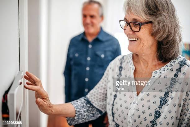 senior vrouw met behulp van domotica aanraakscherm paneel in verpleeghuis - veiligheidsmaatregelen stockfoto's en -beelden