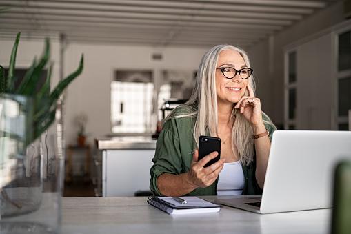 Senior woman using laptop and smartphone 1161412480