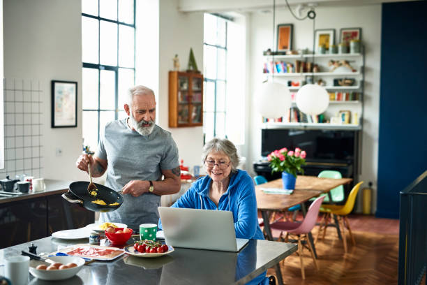 senior woman using laptop and smiling as man serves breakfast - authentic relationship stock pictures, royalty-free photos & images