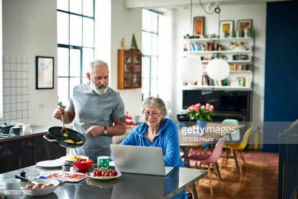 senior woman using laptop and smiling as man serves breakfast - cozinha doméstica imagens e fotografias de stock