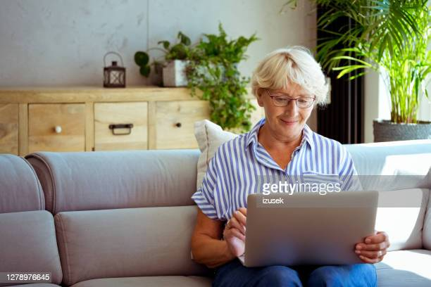 senior woman using laptop at home - laptop stock pictures, royalty-free photos & images