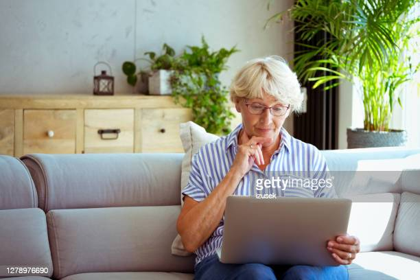 senior woman using laptop at home - the internet stock pictures, royalty-free photos & images